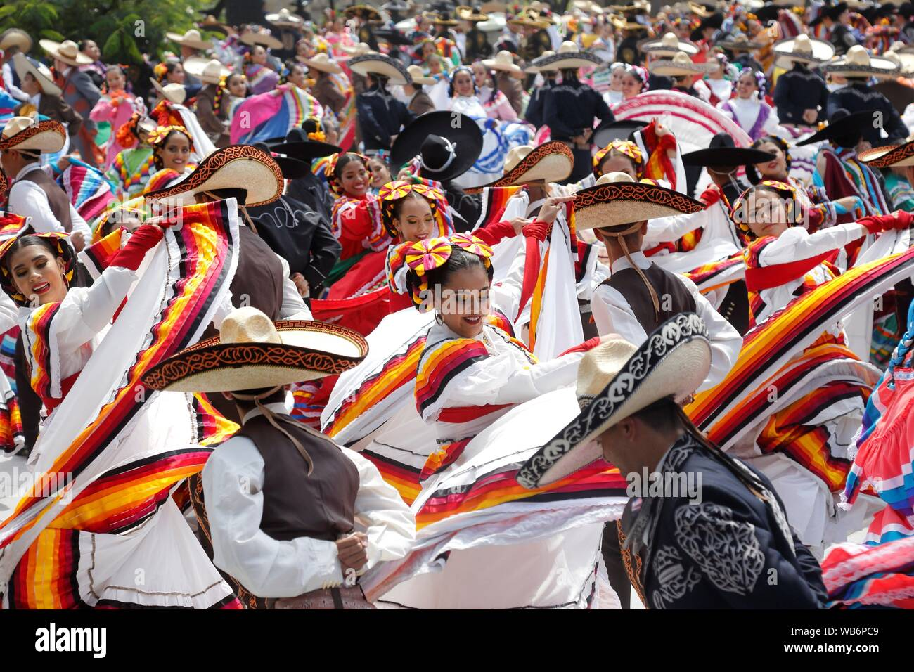 Guadalajara, México. El 25 de agosto, 2019. Unos 882 bailarines rompió el récord Guinness de más grande del mundo de la danza folclórica en Guadalajara, México, 24 de agosto de 2019, como parte del Mariachi y la charreria Reunión Internacional que se celebra hasta el 2 de septiembre. Vestida con trajes tradicionales, los bailarines de todas las edades bailaban al ritmo de la canción tradicional mexicana 'El jarabe tapatío', un icono de esta ciudad, interpretado por un grupo de mariachis que asisten a esta reunión anual. EFE/ Francisco Guasco Crédito: Agencia de Noticias EFE/Alamy Live News Foto de stock