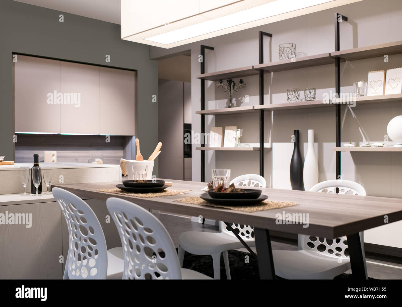 Cocina y comedor con decoración beige neutro, Estanterías de pared y una moderna unidad de sillas y mesa iluminada por una gran sobrecarga de luz de techo Foto de stock