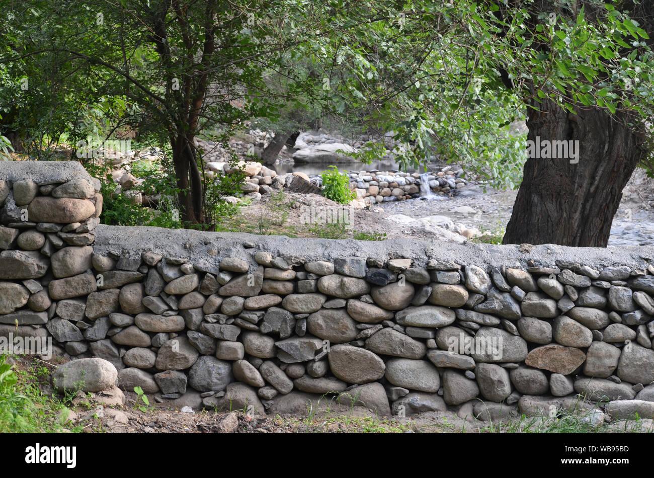 Muro de piedra de un huerto cerca de la aldea de Sentyab en las montañas de Nurata, central de Uzbekistán Foto de stock