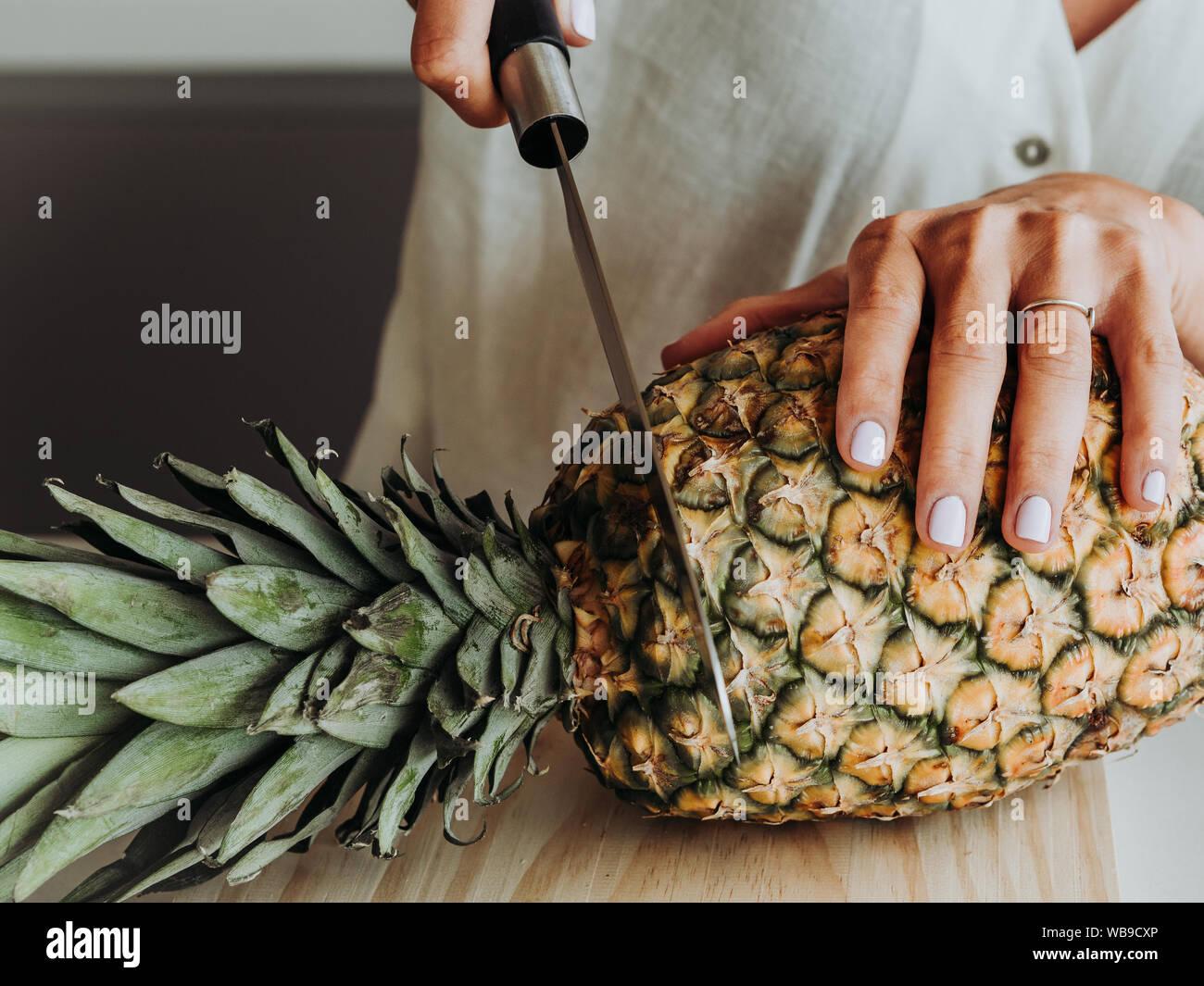 Mujer rubia y de ojos verdes en la cocina moderna y la acerca a preparar una piña. Foto de stock