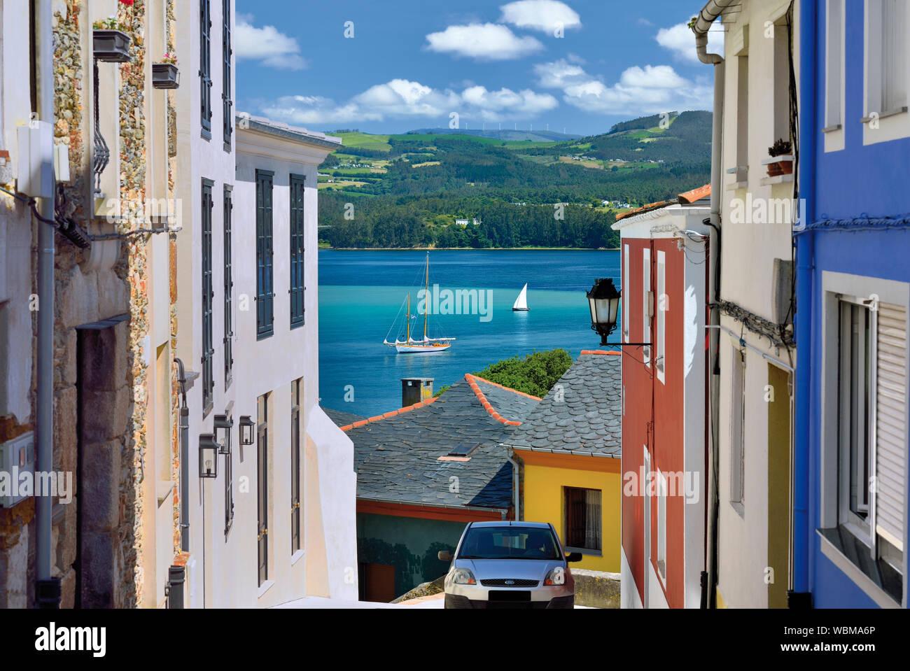 Hermosa vista desde un callejón estrecho a bahía con veleros fondeando en el agua Foto de stock