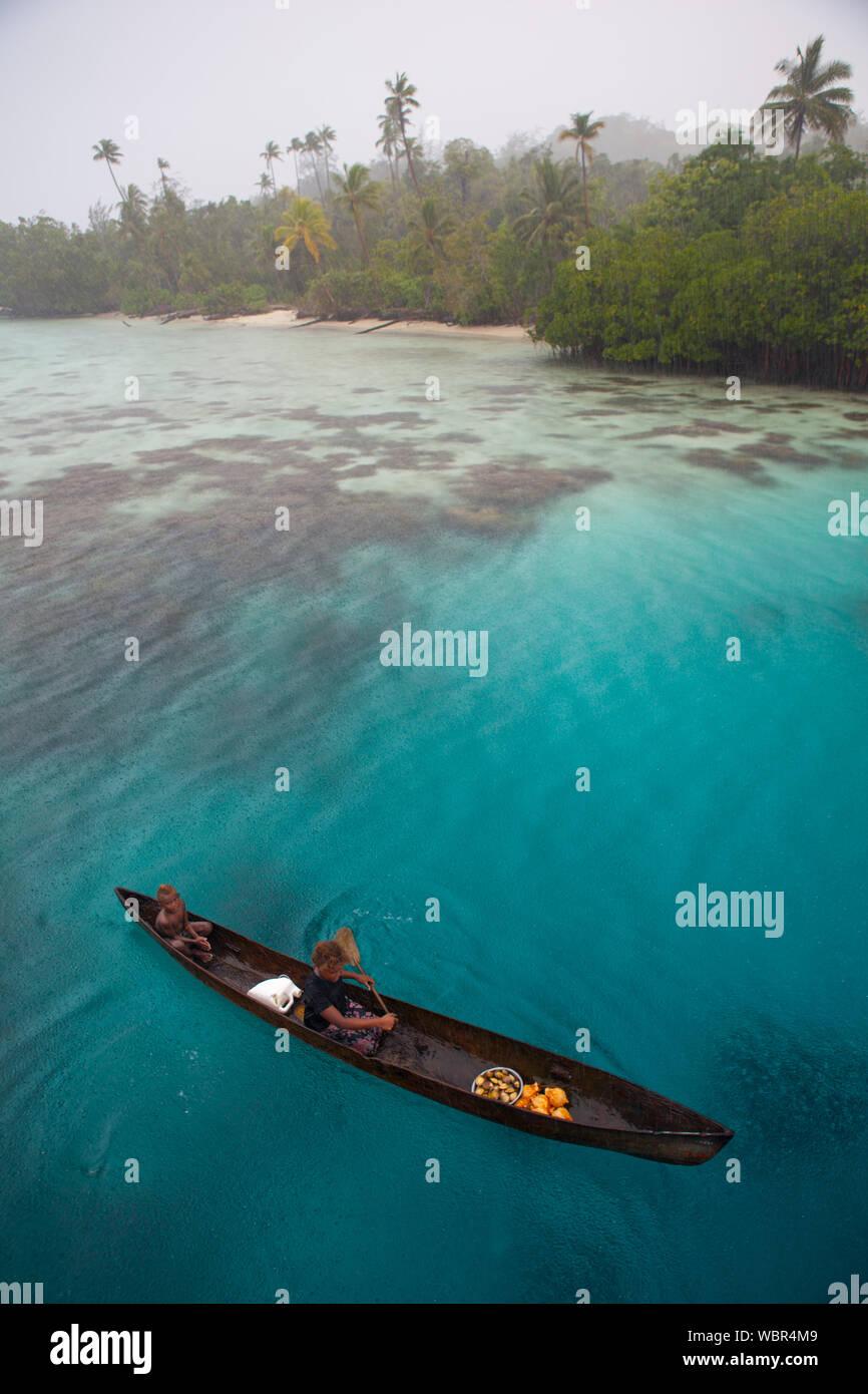 Los niños melanesios paddle su canoa en la lluvia, en medio de las hermosas Islas Salomón. Esta región melanesia es parte del triángulo de Coral. Foto de stock