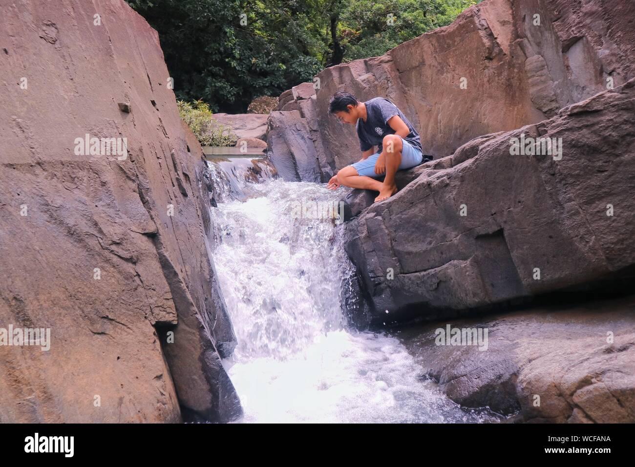 Vista trasera de la joven mujer de pie sobre un acantilado por Cascada Foto de stock