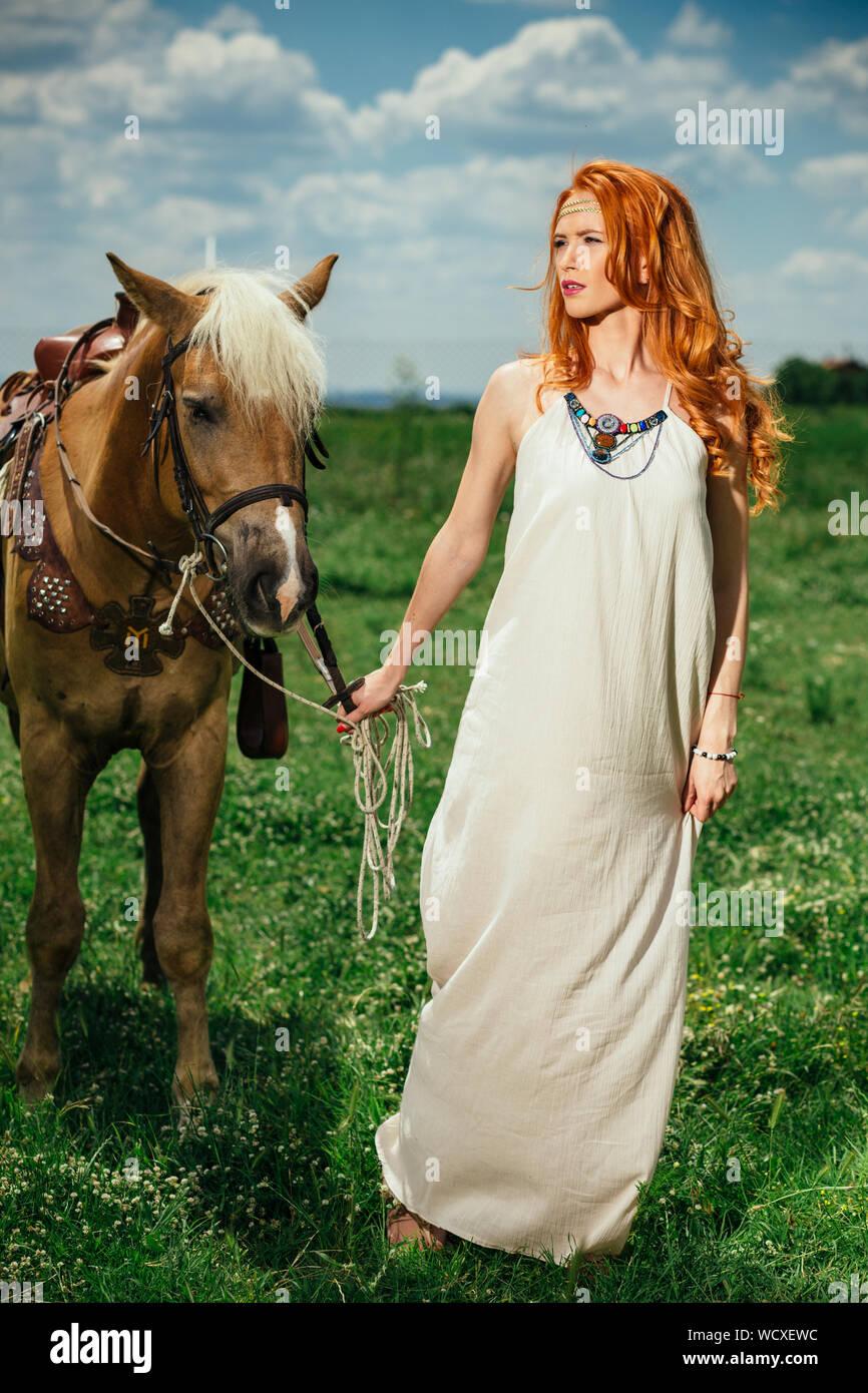 La longitud completa de la hermosa mujer con caballo parado sobre Césped contra Sky Foto de stock