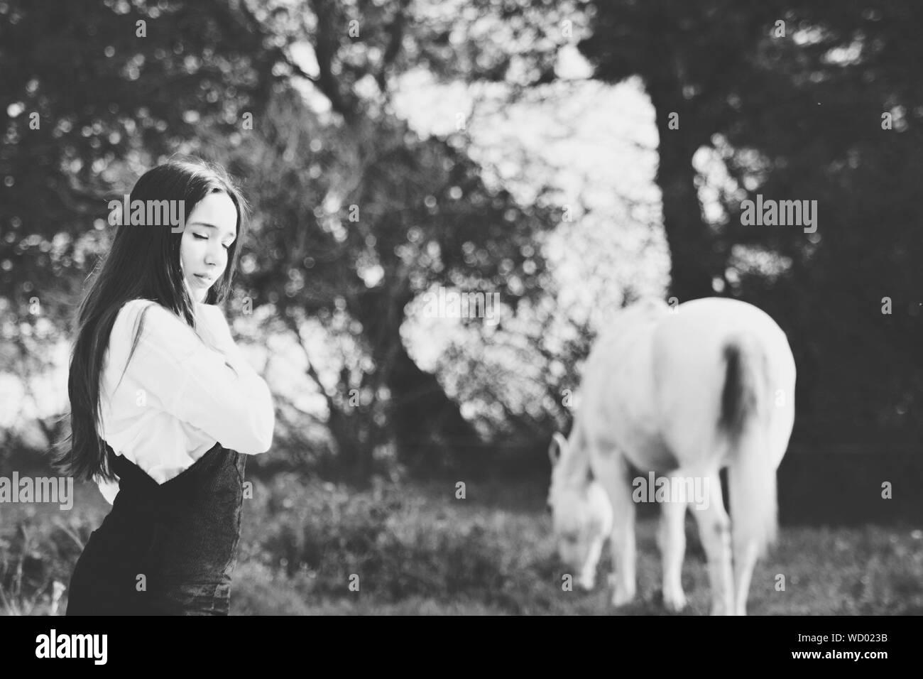 Mujer de pie con los ojos cerrados a caballo en el campo Foto de stock