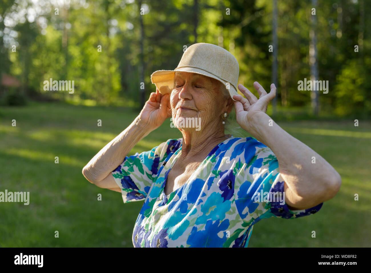 Senior mujer vistiendo sombrero para el sol en el campo Foto de stock