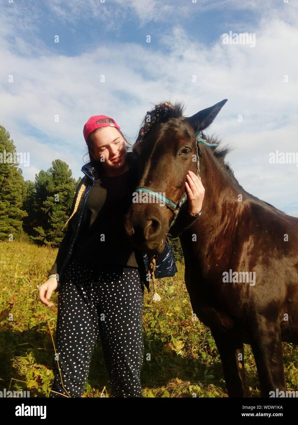 Mujer joven con caballo parado en el campo contra el cielo Foto de stock