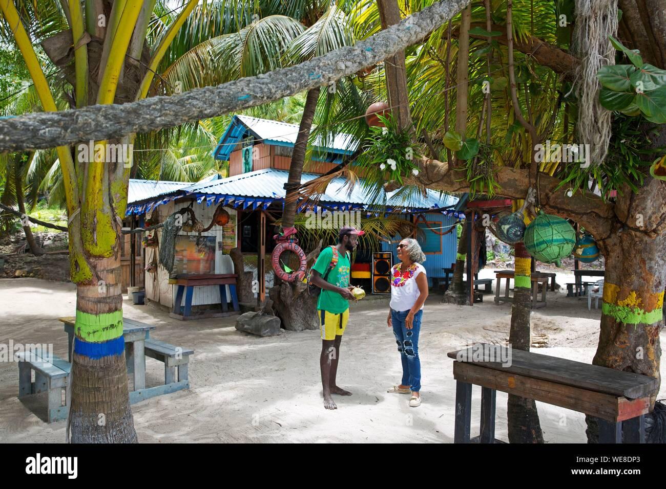 Colombia, la isla de Providencia, Colombia pareja conversando sobre la arena de Rolland's bar, un bar oculto bajo la vegetación tropical en la playa de Manzanillo Foto de stock