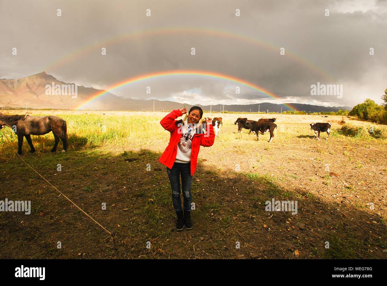 Mujer de pie feliz por caballos y vacas contra el Arco iris sobre el campo Foto de stock