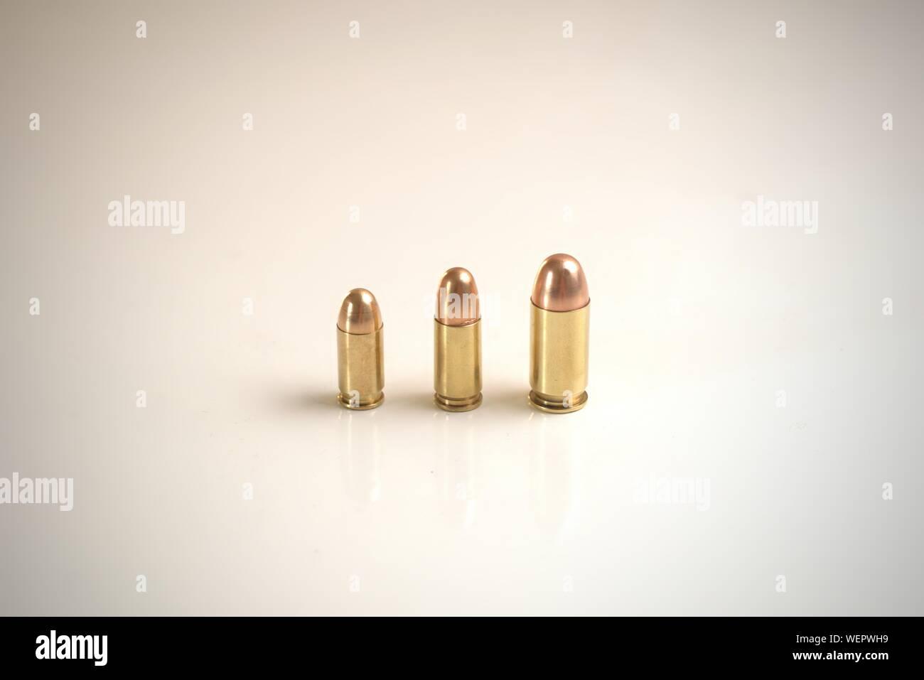 Tres balas de distintos calibres sobre una superficie blanca. De izquierda a derecha: .380 FMJ automático 9x19mm FMJ .45 Auto FMJ Foto de stock