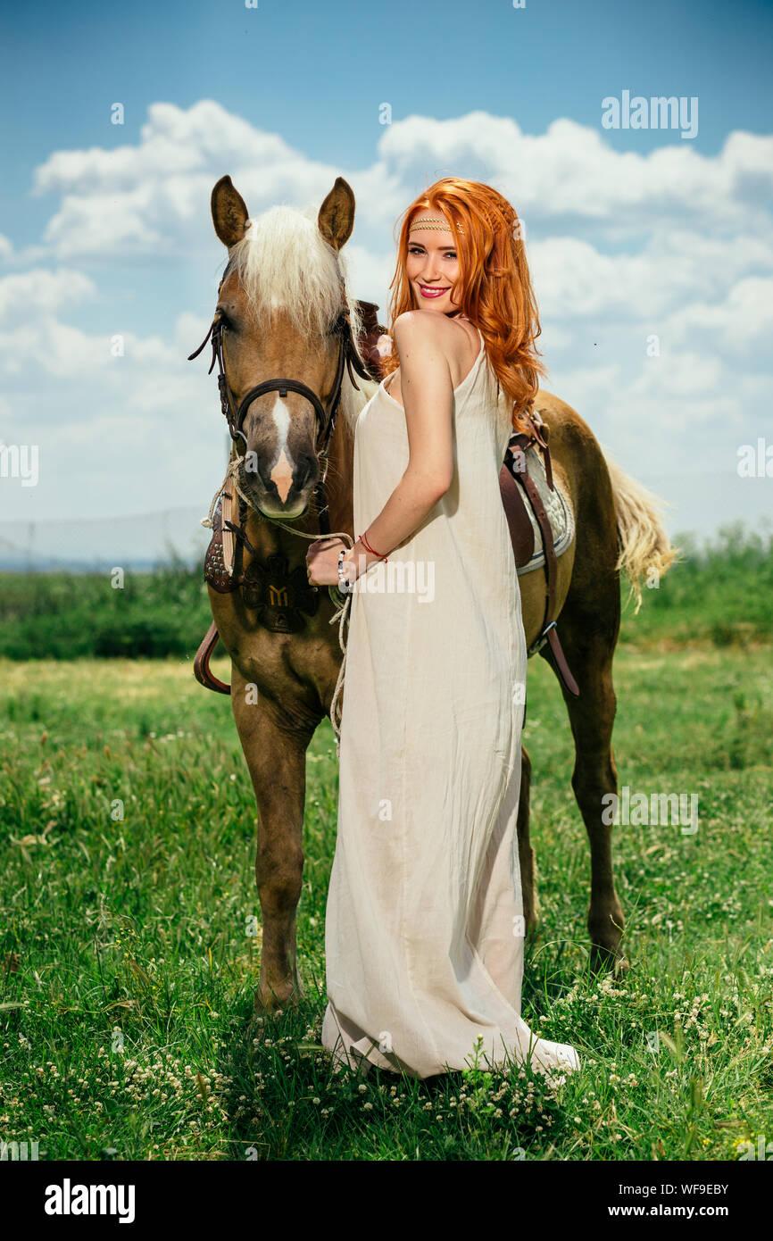 Longitud total retrato de mujer hermosa con el caballo parado en el campo de hierba contra el cielo Foto de stock