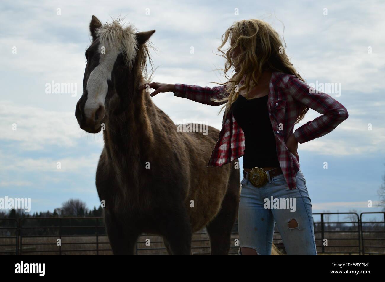 Mujer con caballo marrón de pie en campo Foto de stock