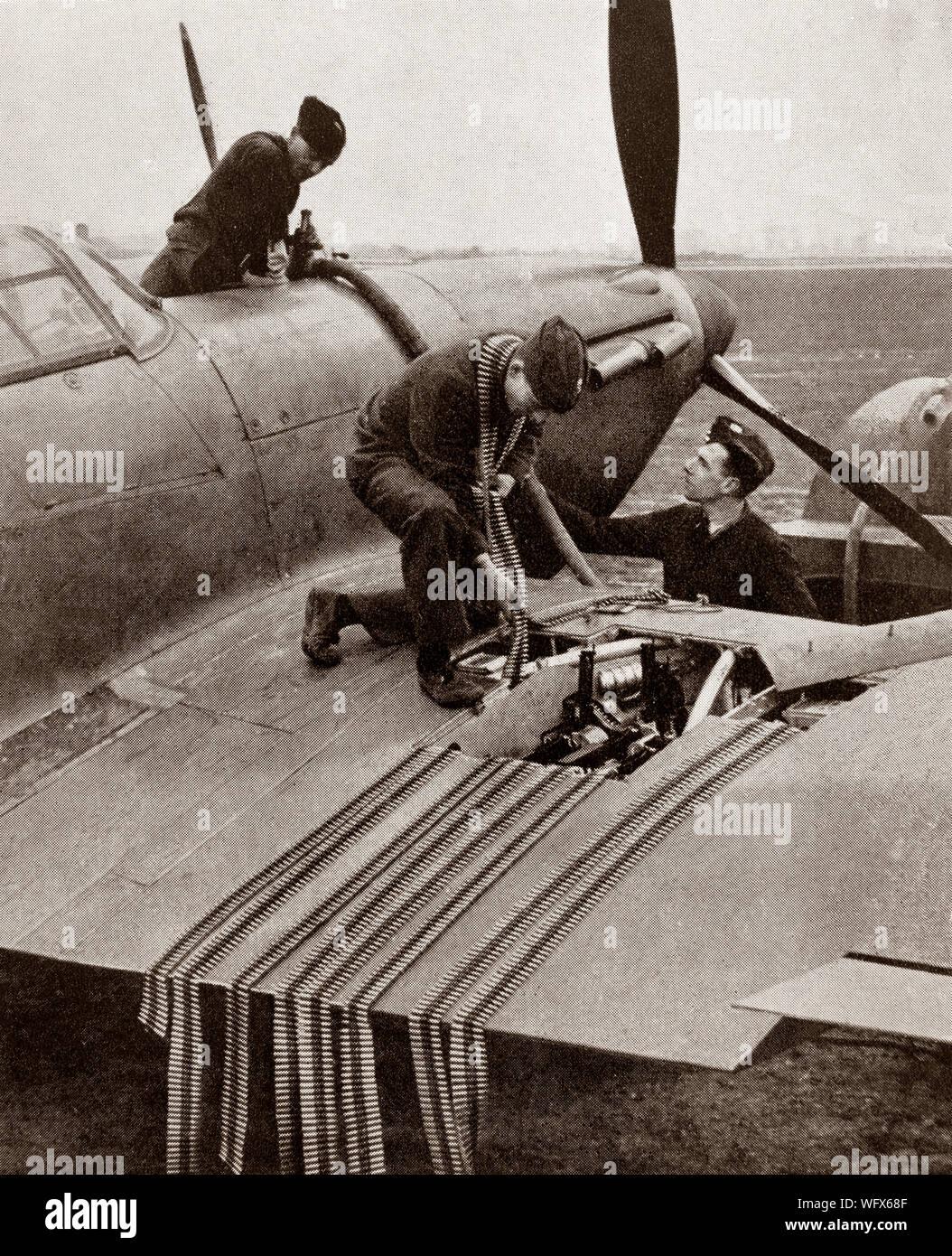 Groundcrew cargando munición en el ala de un huracán, los británicos Hawker Solo asiento con aviones de combate de la RAF. Se vio ensombrecida en la conciencia pública por el Supermarine Spitfire el papel durante la Batalla de Gran Bretaña en 1940, pero el Huracán infligió el 60 por ciento de las pérdidas sufridas por la Luftwaffe en la contratación, y luchó en todos los principales teatros de la Segunda Guerra Mundial. Foto de stock