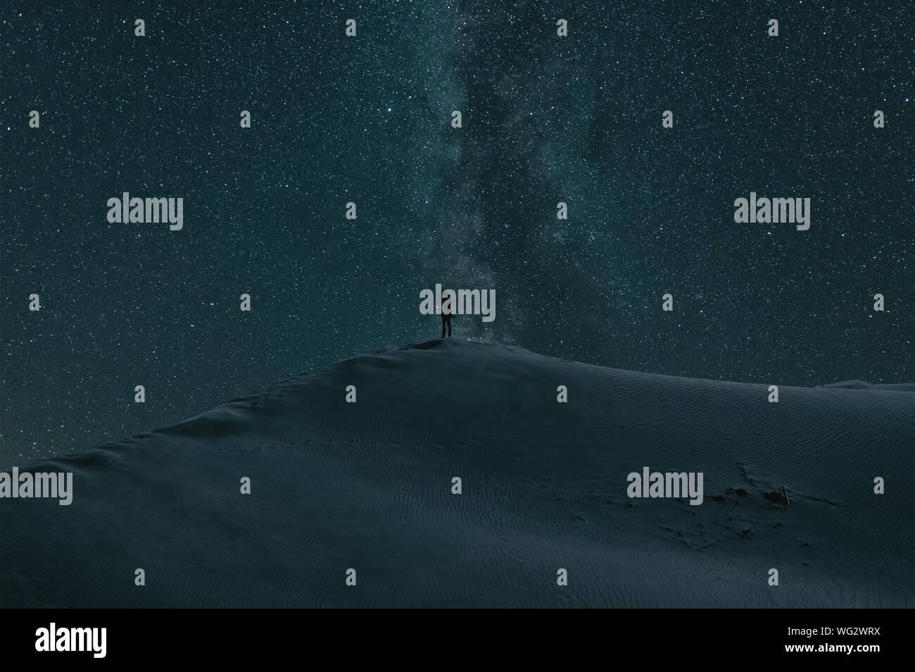 Persona de pie sobre el paisaje cubierto de nieve contra el campo de estrellas Foto de stock