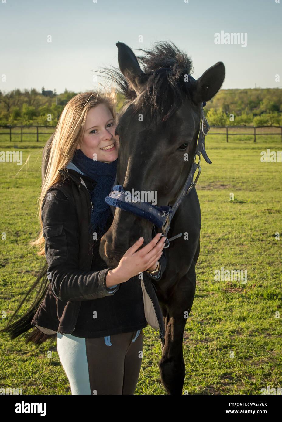 Retrato de mujer sonriente de pie con caballo en campo de hierba en la granja Foto de stock