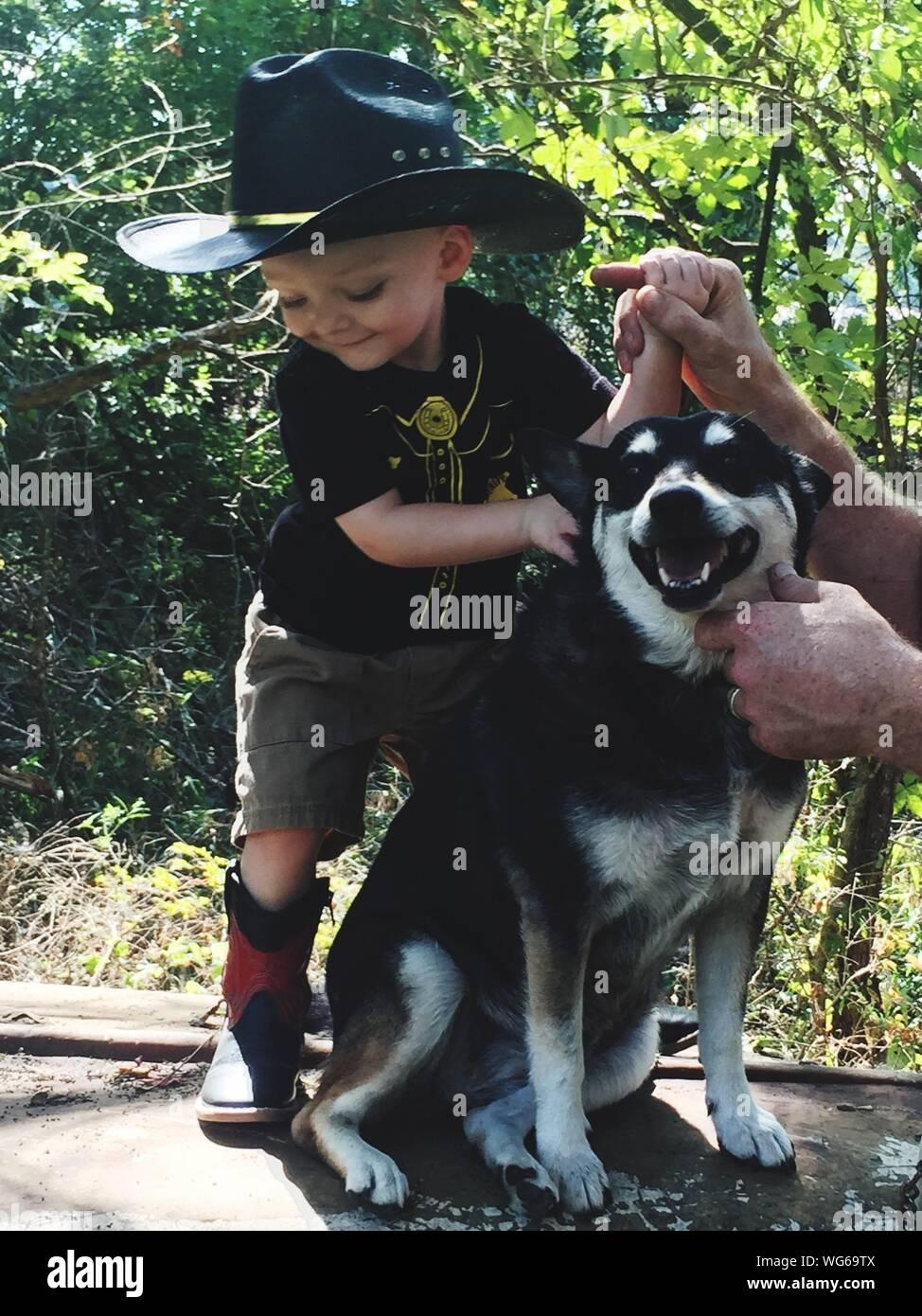 Hombre sujetando Infante por perro contra plantas Foto de stock