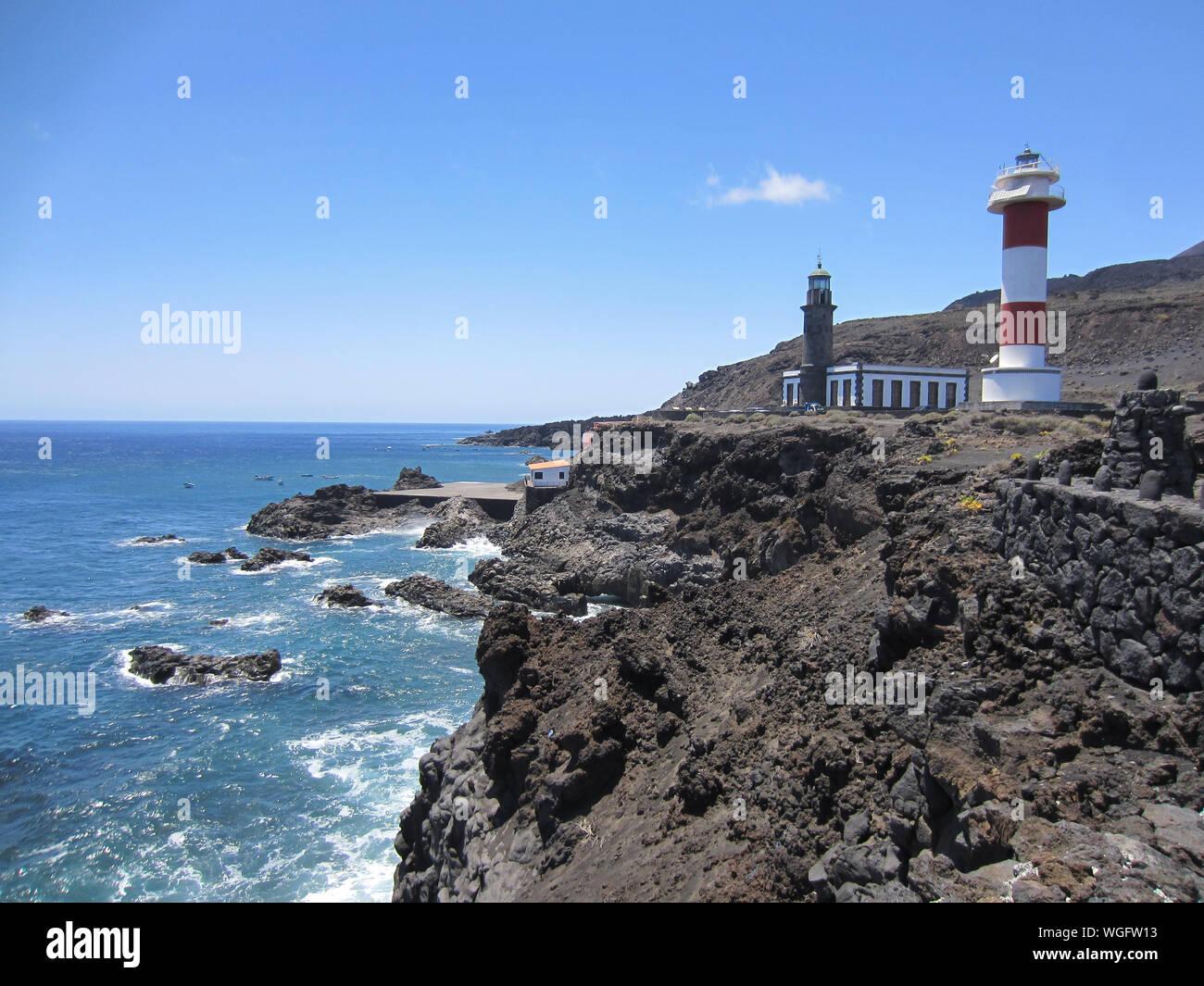 Faro en la playa contra el cielo azul claro Foto de stock