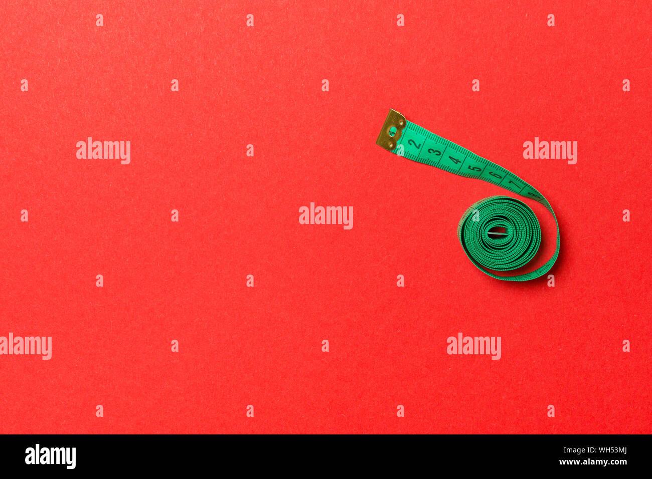 Vista superior de la cinta de medir, doblada en una espiral con espacio de copia. Concepto de accesorios de costura o dieta saludable sobre fondo rojo. Foto de stock