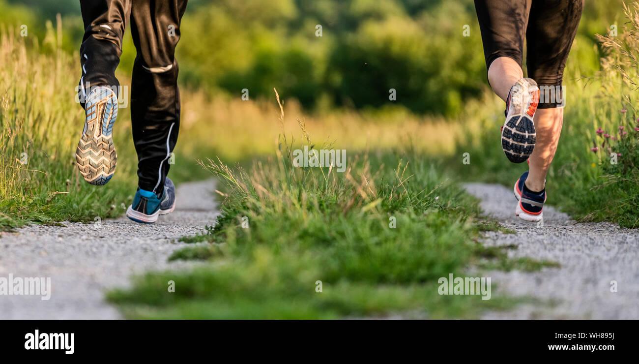 Las piernas del hombre y de la mujer correr Foto de stock