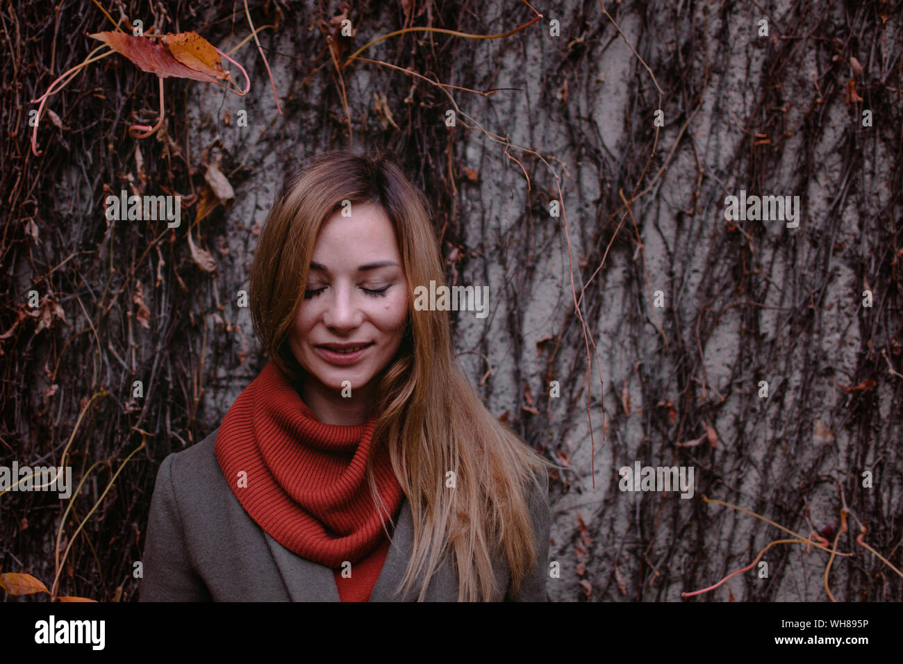 Retrato de mujer sonriente con los ojos cerrados en otoño Foto de stock