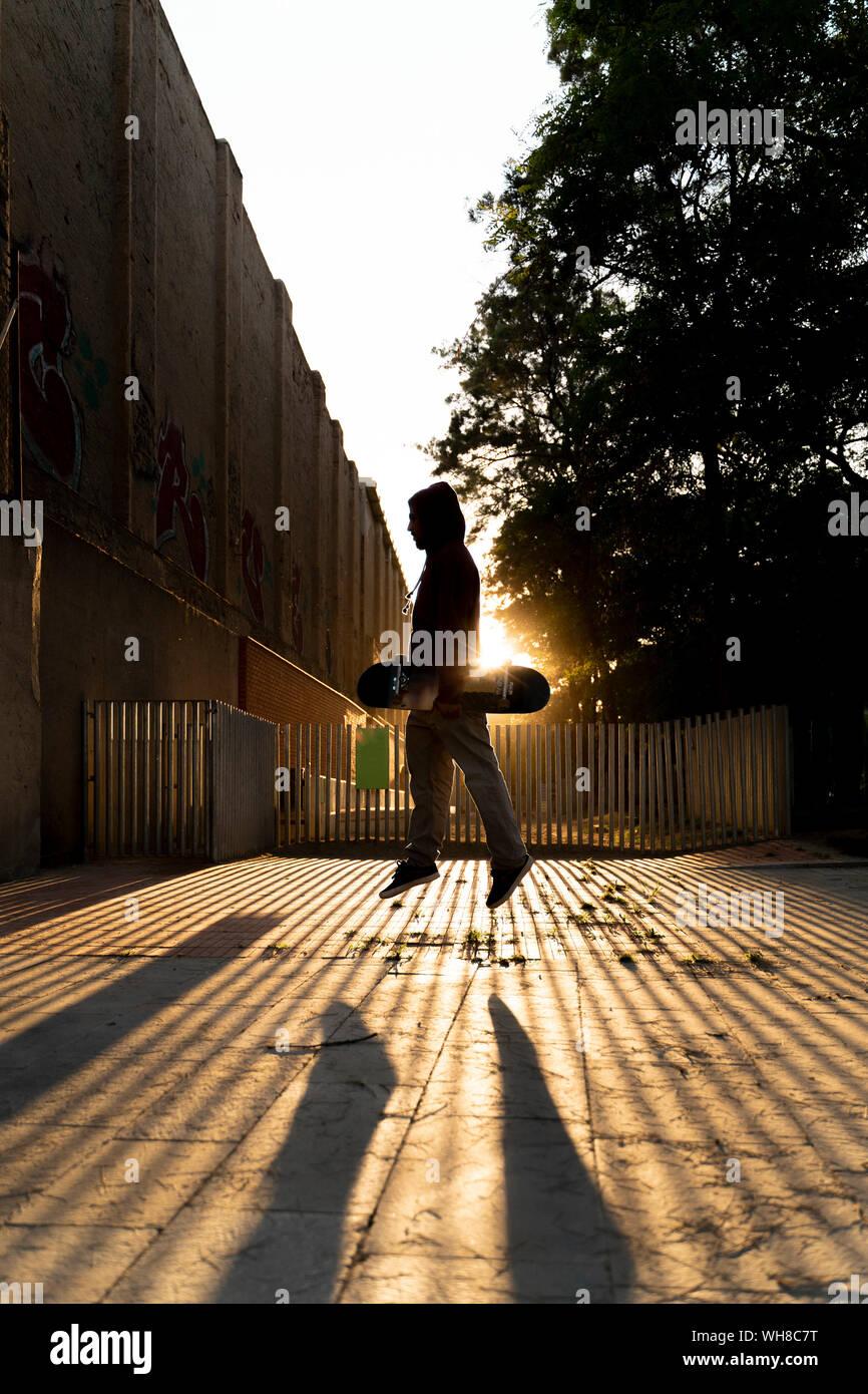 Silueta de la patinadora saltar en el aire a contraluz Foto de stock