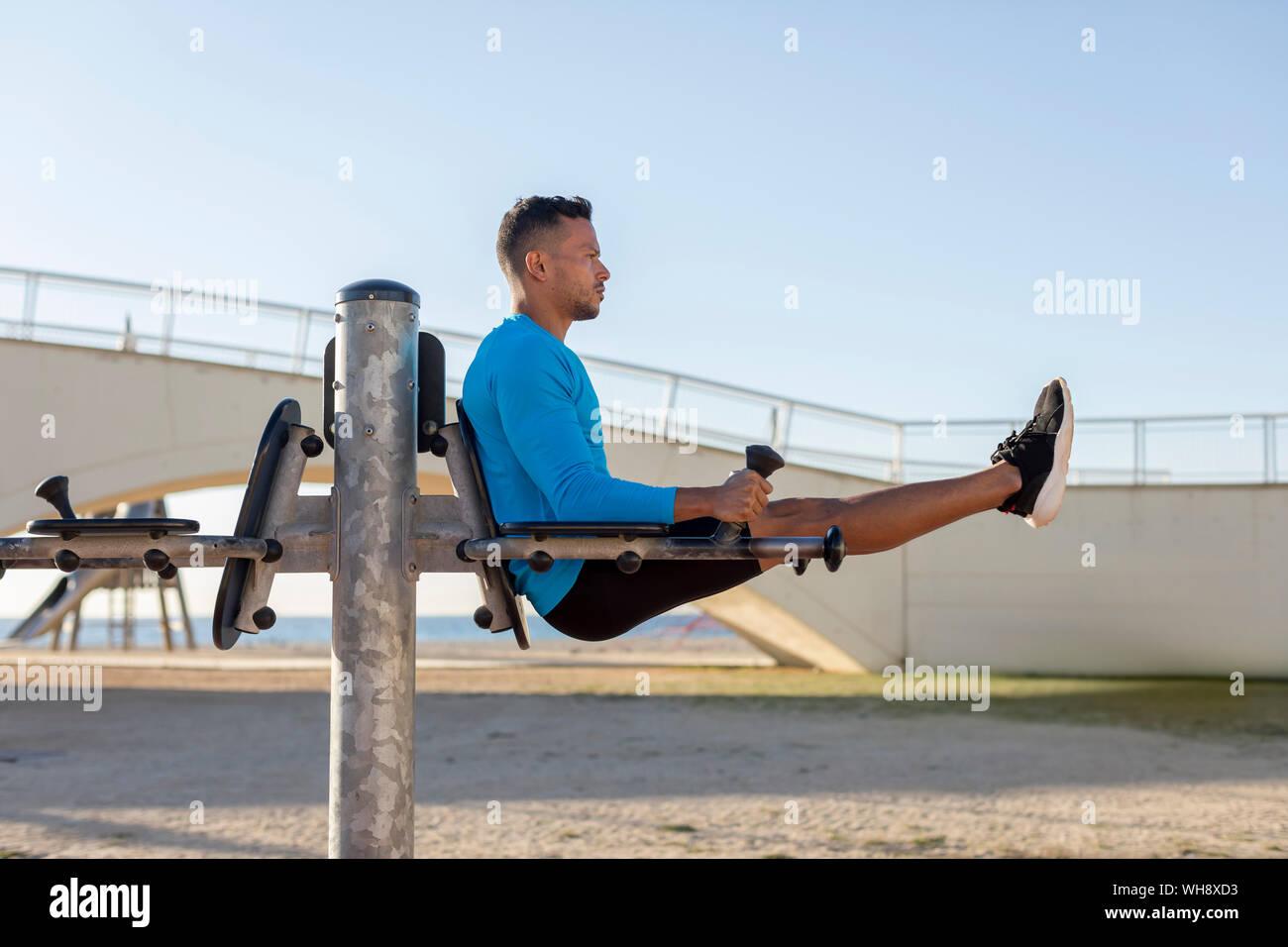 Hombre haciendo ejercicio en equipo para hacer ejercicio al aire libre Foto de stock