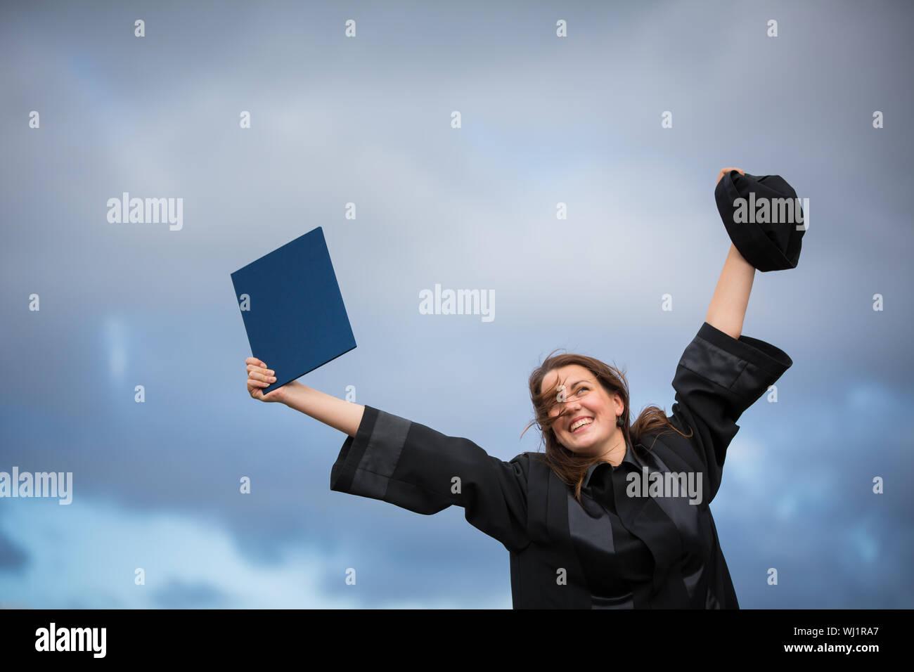 Bastante joven, celebrando con alegría su graduación - difusión amplia sus brazos, sosteniendo su diploma, saboreando su éxito (la imagen en tonos de color; shal Foto de stock