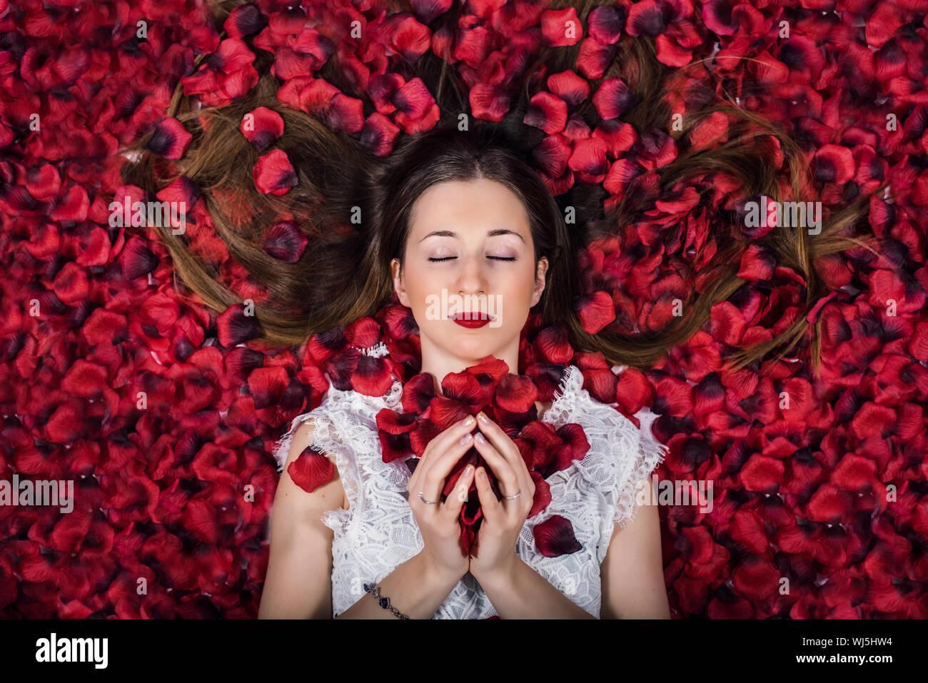 Directamente encima de foto de mujer acostada sobre Pétalos de Rosas Foto de stock