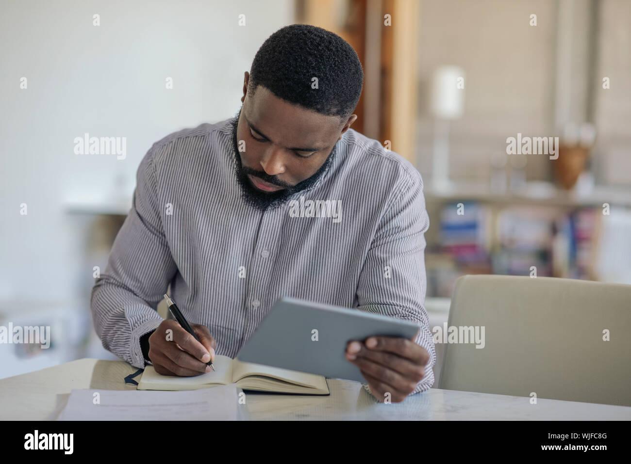 Joven hombre afroamericano utilizando una tableta digital en casa Foto de stock