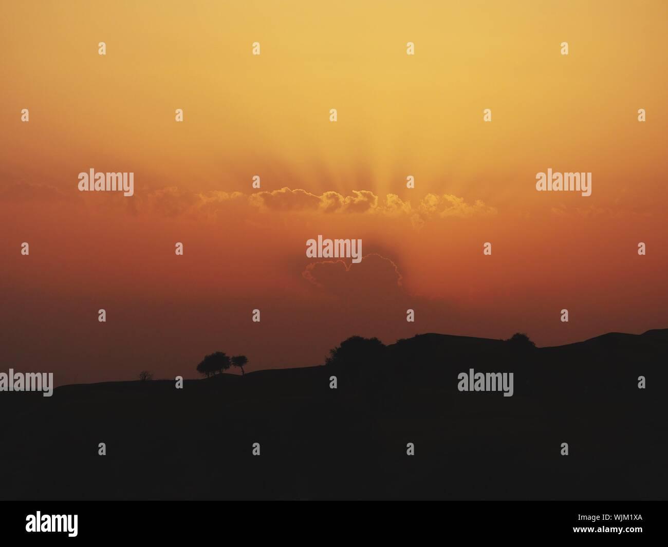 Vista panorámica del paisaje de silueta contra el cielo durante la puesta de sol Foto de stock