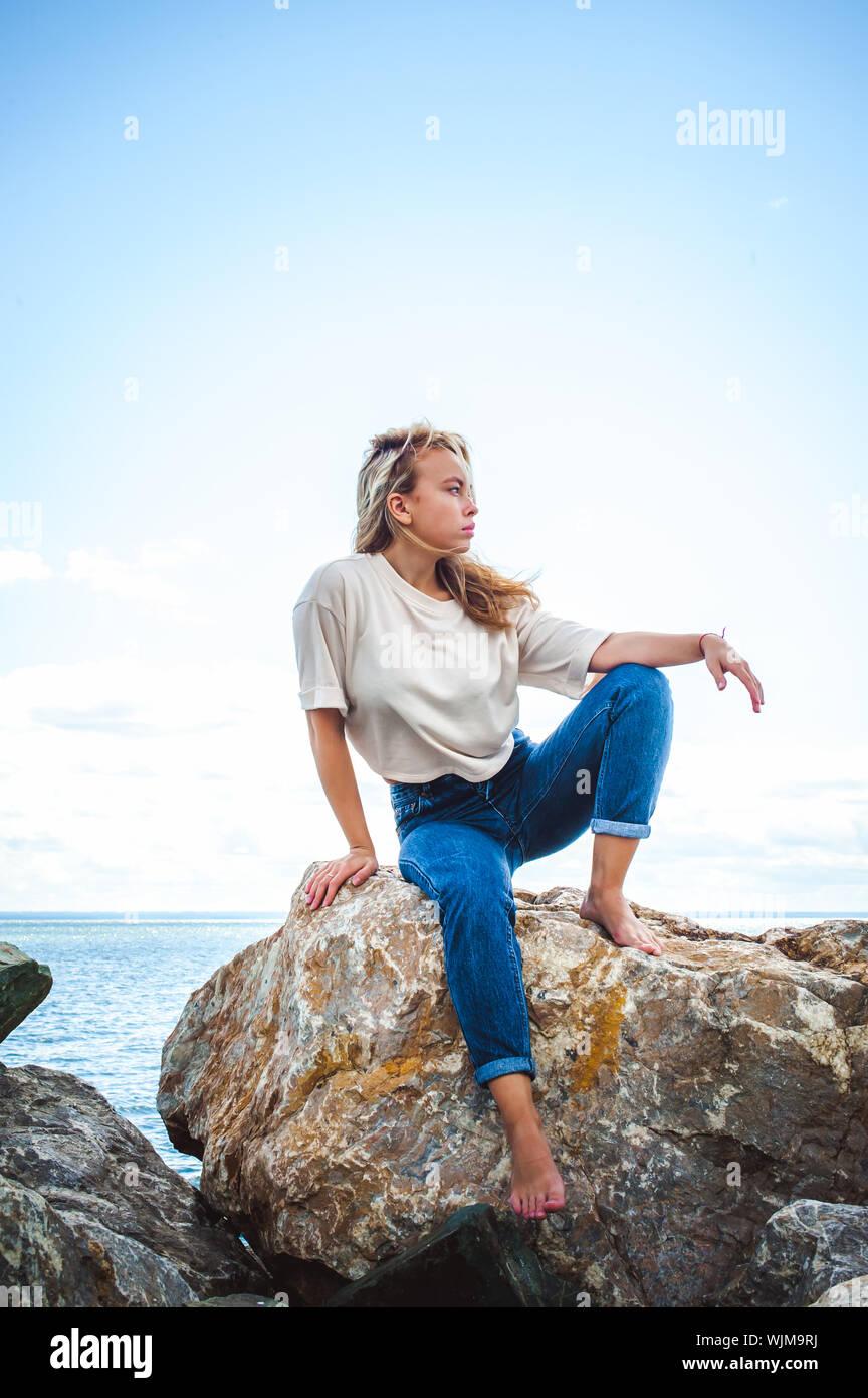 Mujer joven de pie sobre la roca en la orilla del mar contra el cielo Foto de stock