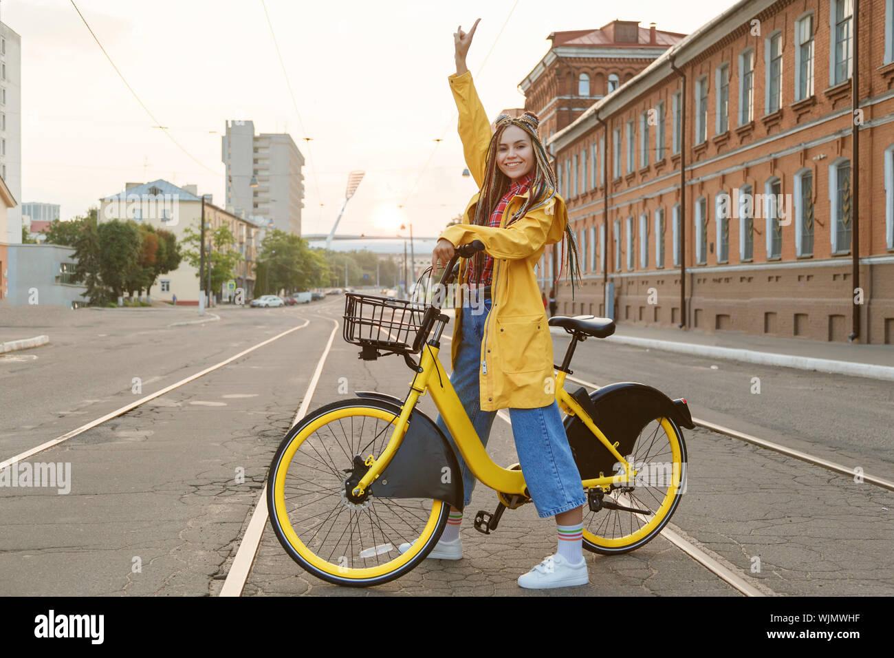 Mujer joven vistiendo abrigo color amarillo y pigtails, montando en bicicleta en la ciudad. Foto de stock