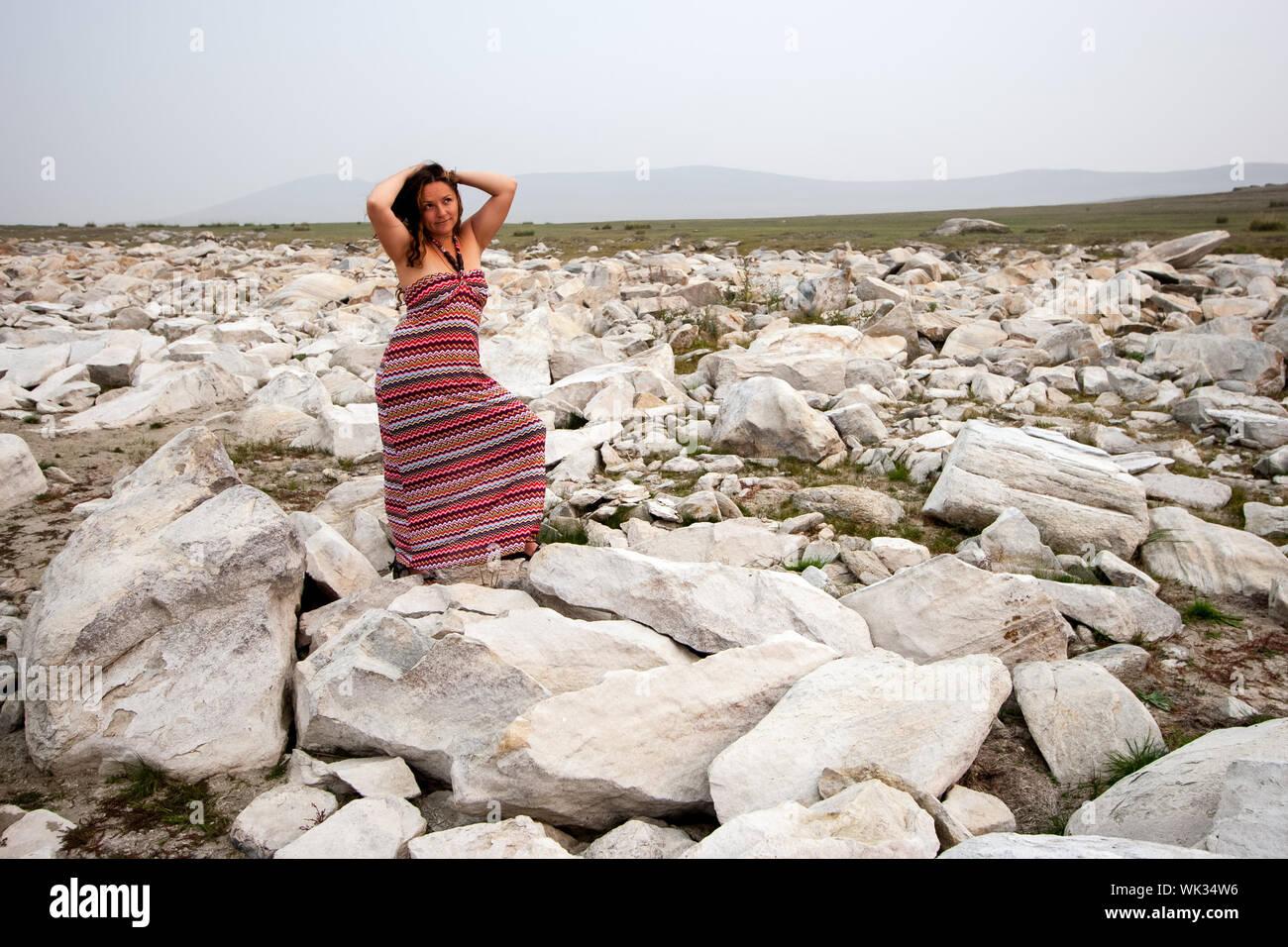 Una chica con cabello oscuro destaca sobre piedras blancas en la estepa y mira hacia arriba. Manos tocaron la cabeza. Traje a rayas rojas. Detrás de la niebla. Copie el espacio. Foto de stock