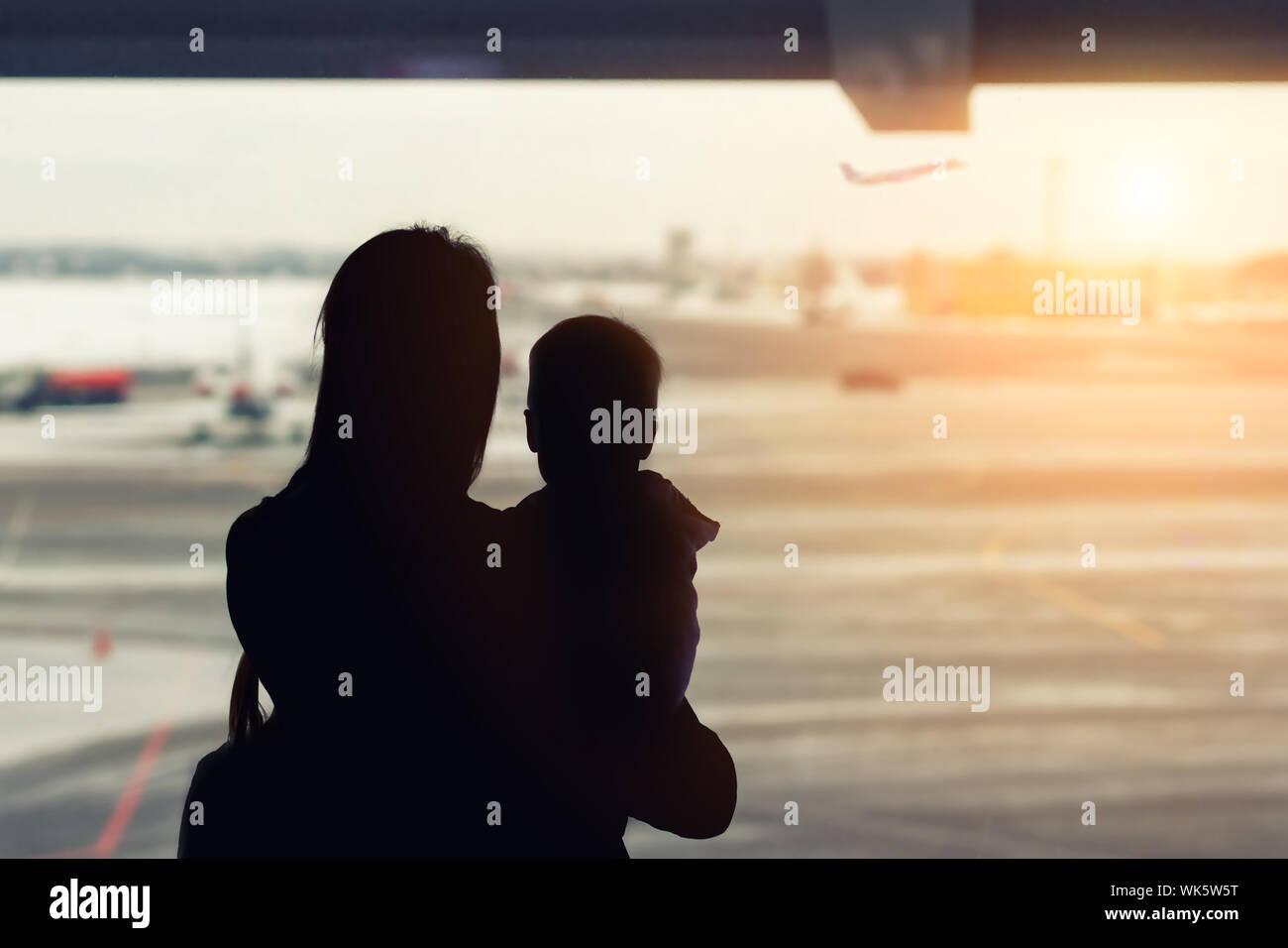 Silueta de madre sosteniendo en las manos poco niño chico con ventana de aeropuerto en segundo plano. La salida y la llegada. Madre soltera con hijo Foto de stock