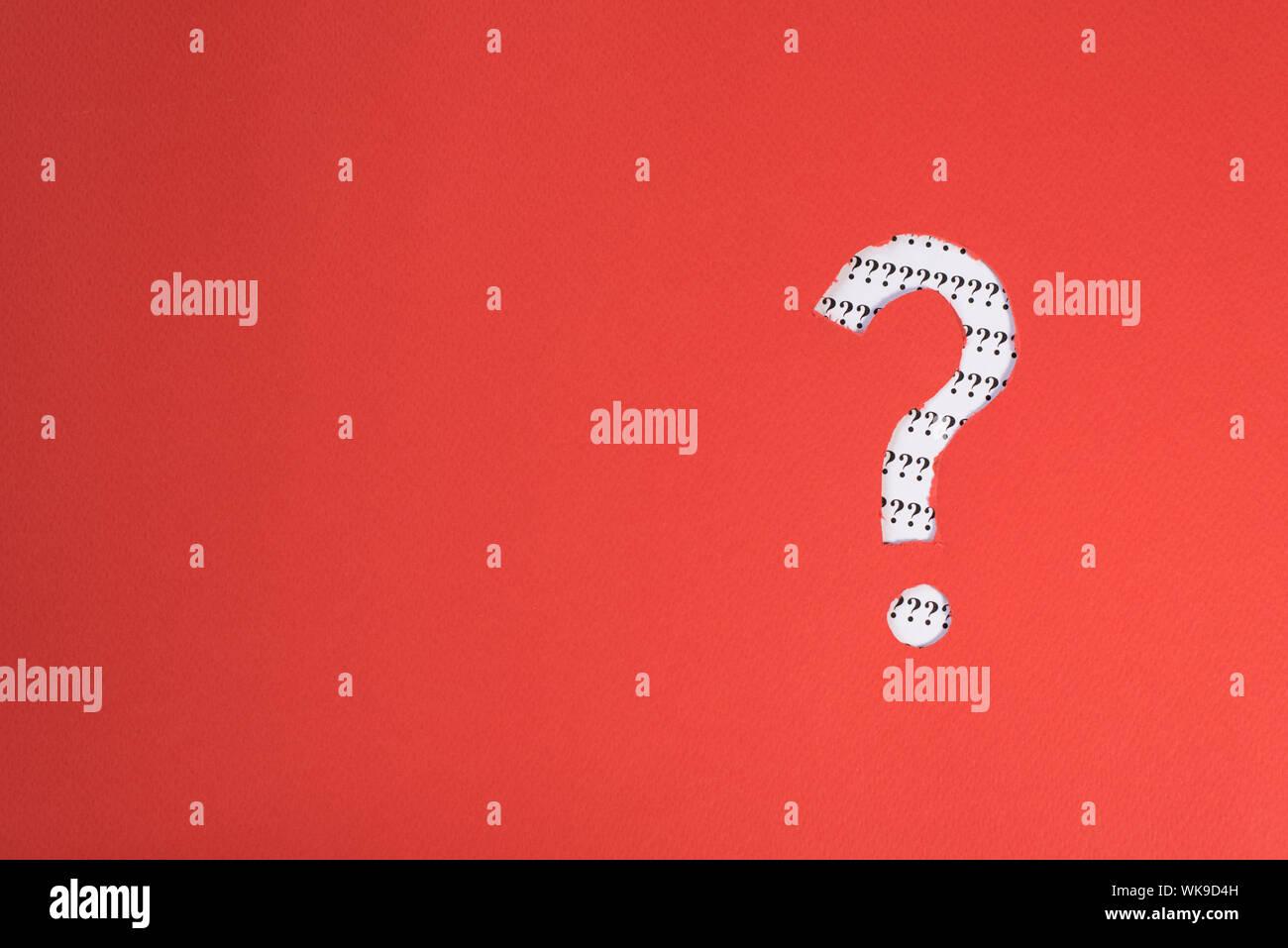 Papel rojo teared a símbolo de interrogación revelando más interrogación sobre papel blanco. Concepto de FAQ, Q&A, buscar riddle e información Foto de stock