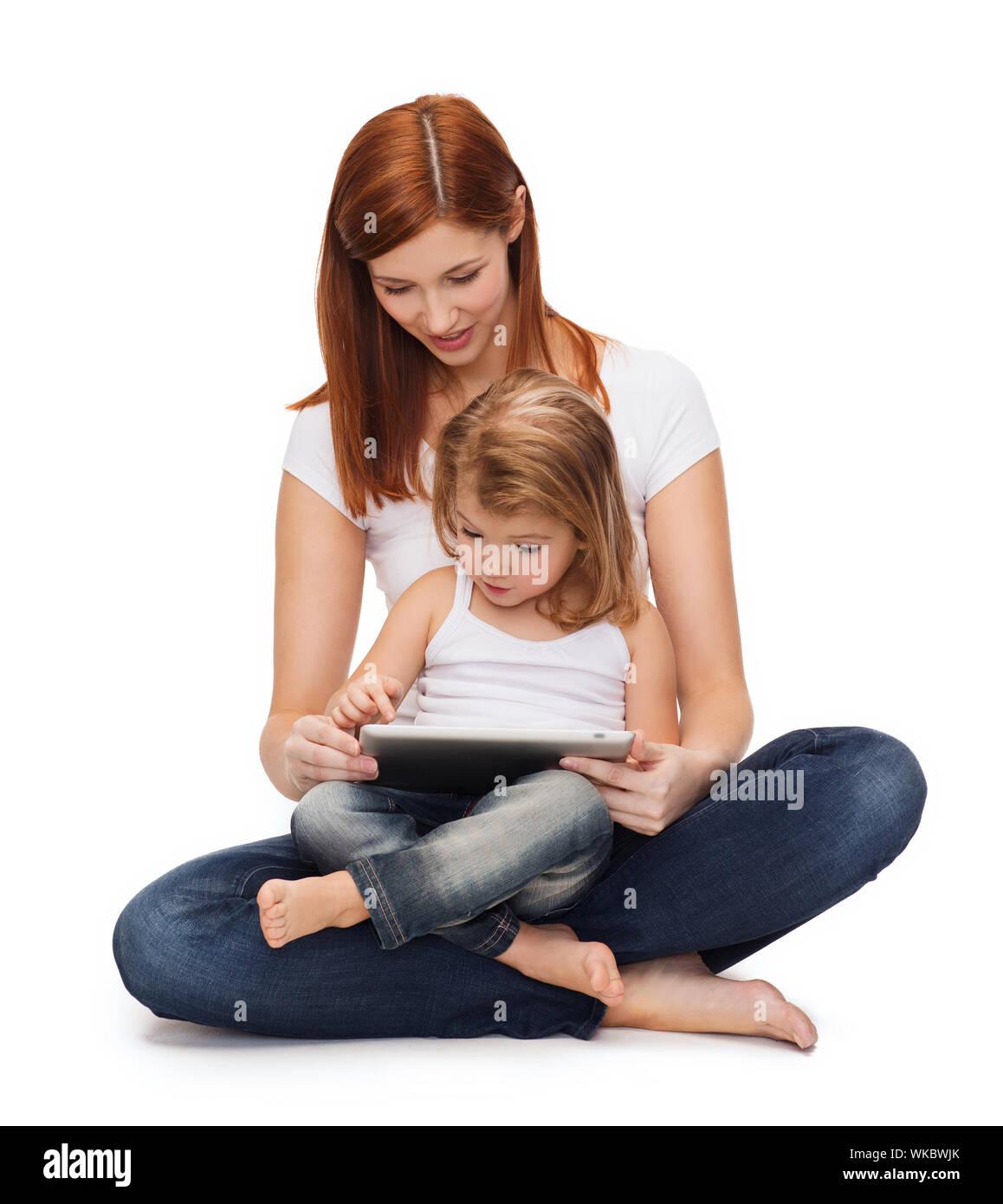 Feliz madre con niña y tablet pc Foto de stock