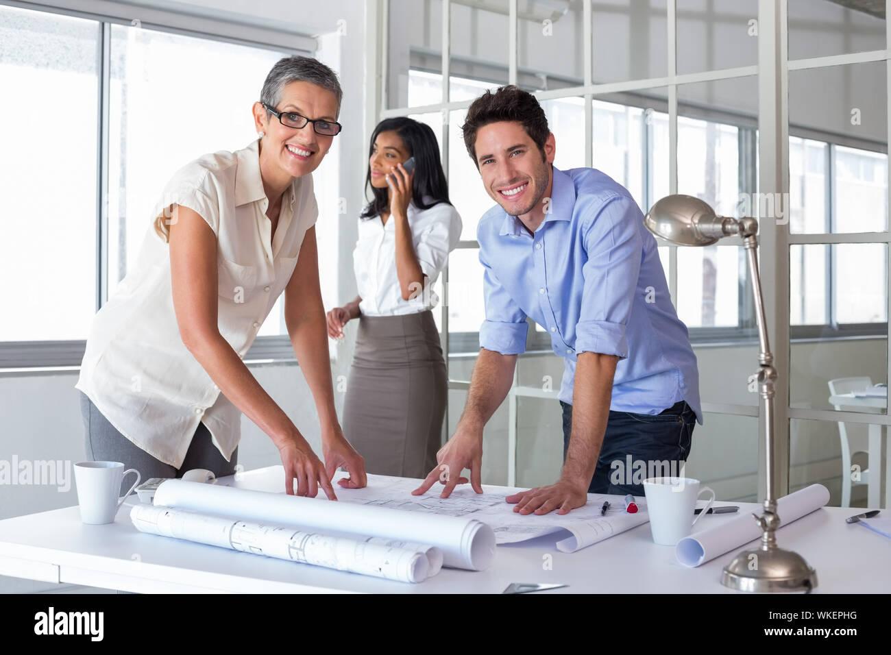 Arquitectos atractiva pasando por planes en la oficina Foto de stock