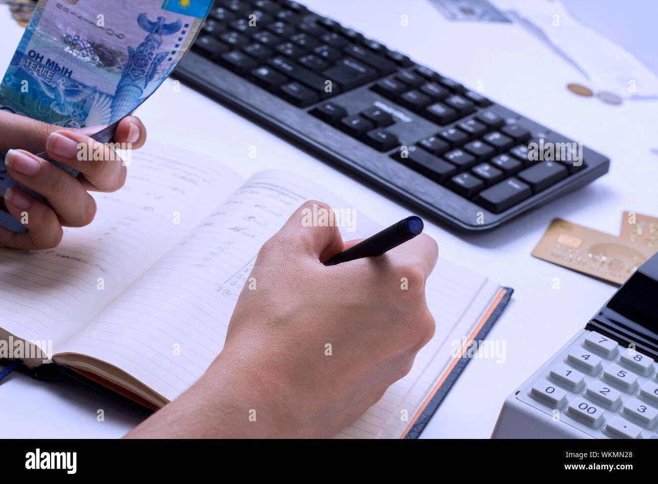 Los resultados de los sueldos en Kazajstán. Contador cajero cuenta el dinero en tenge y llena los informes y declaraciones. Foto de stock