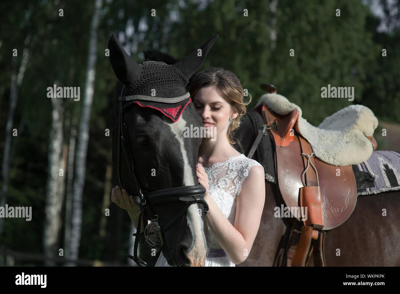 Mujer joven de pie a caballo en el campo durante el día soleado Foto de stock