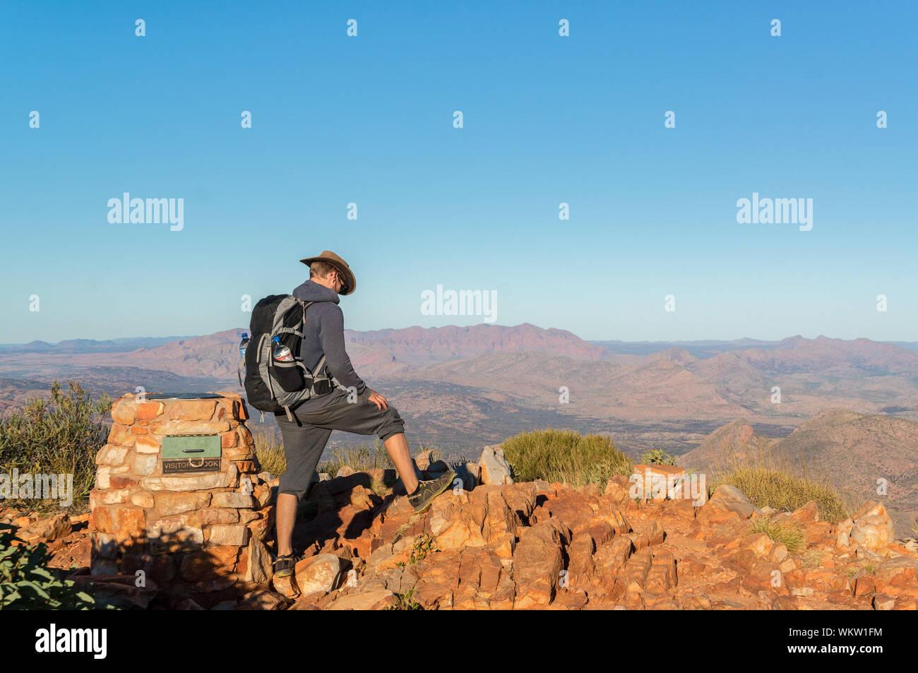 El hombre disfruta de la vista después de una caminata hasta la cima del monte Sonder justo en las afueras de Alice Springs, West MacDonnel National Park, Australia Foto de stock
