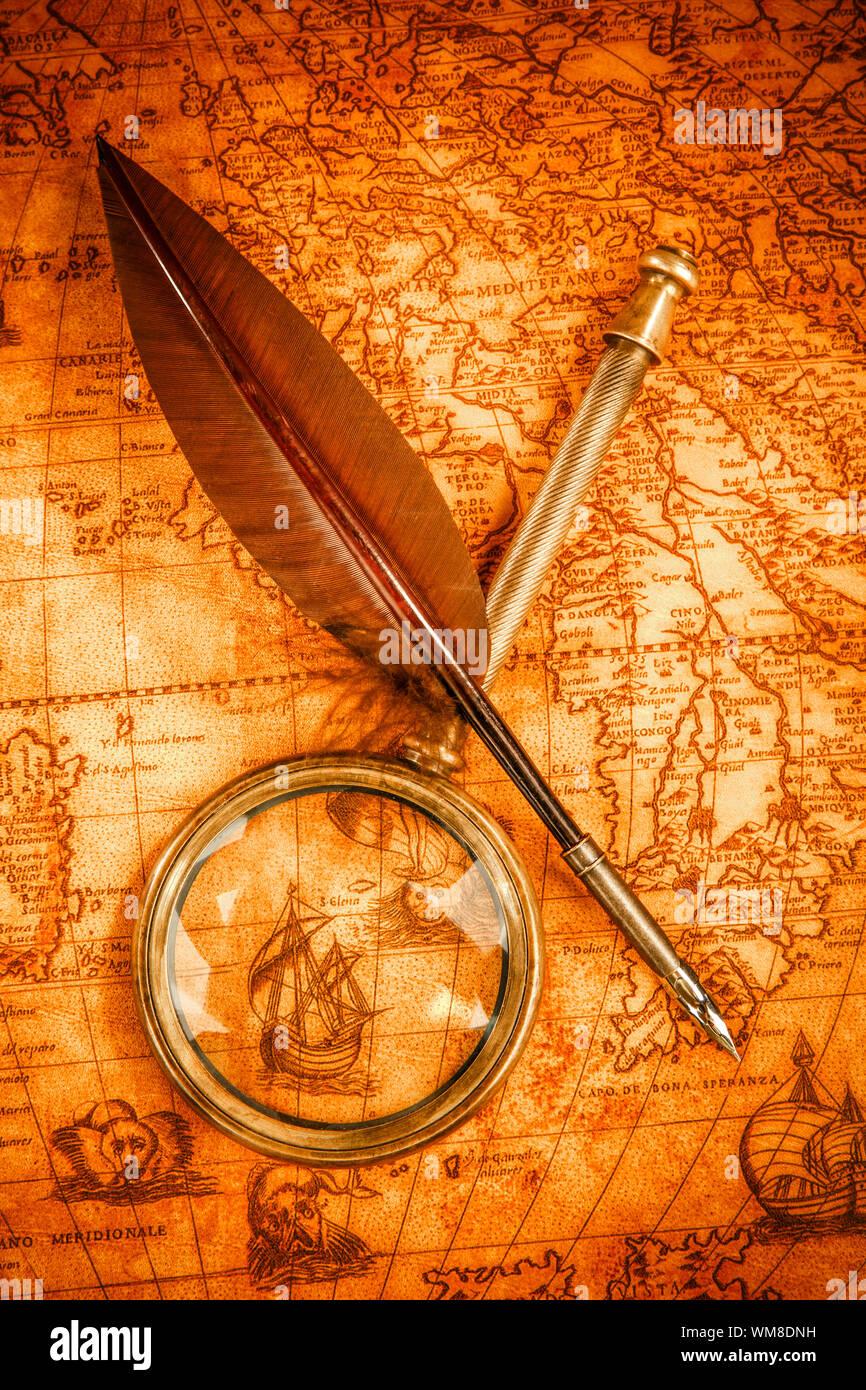 Vintage lupa y quill pen sobre un antiguo mapa en 1565. Vintage todavía la vida. Foto de stock