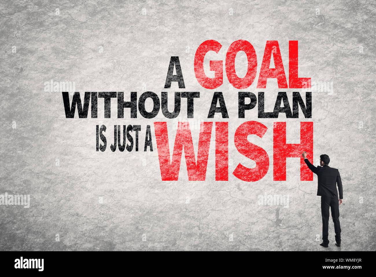 Hombre de negocios asiáticos escribir palabras en la pared, un objetivo sin un plan es sólo un deseo Foto de stock