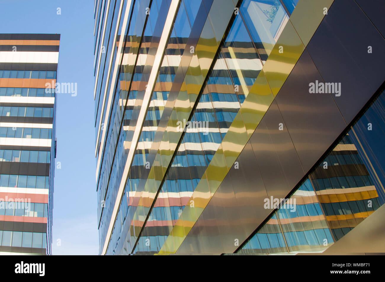Moderna fachada de los edificios con líneas, colores y modelo reflejado en una pared de vidrio contra el cielo azul Foto de stock