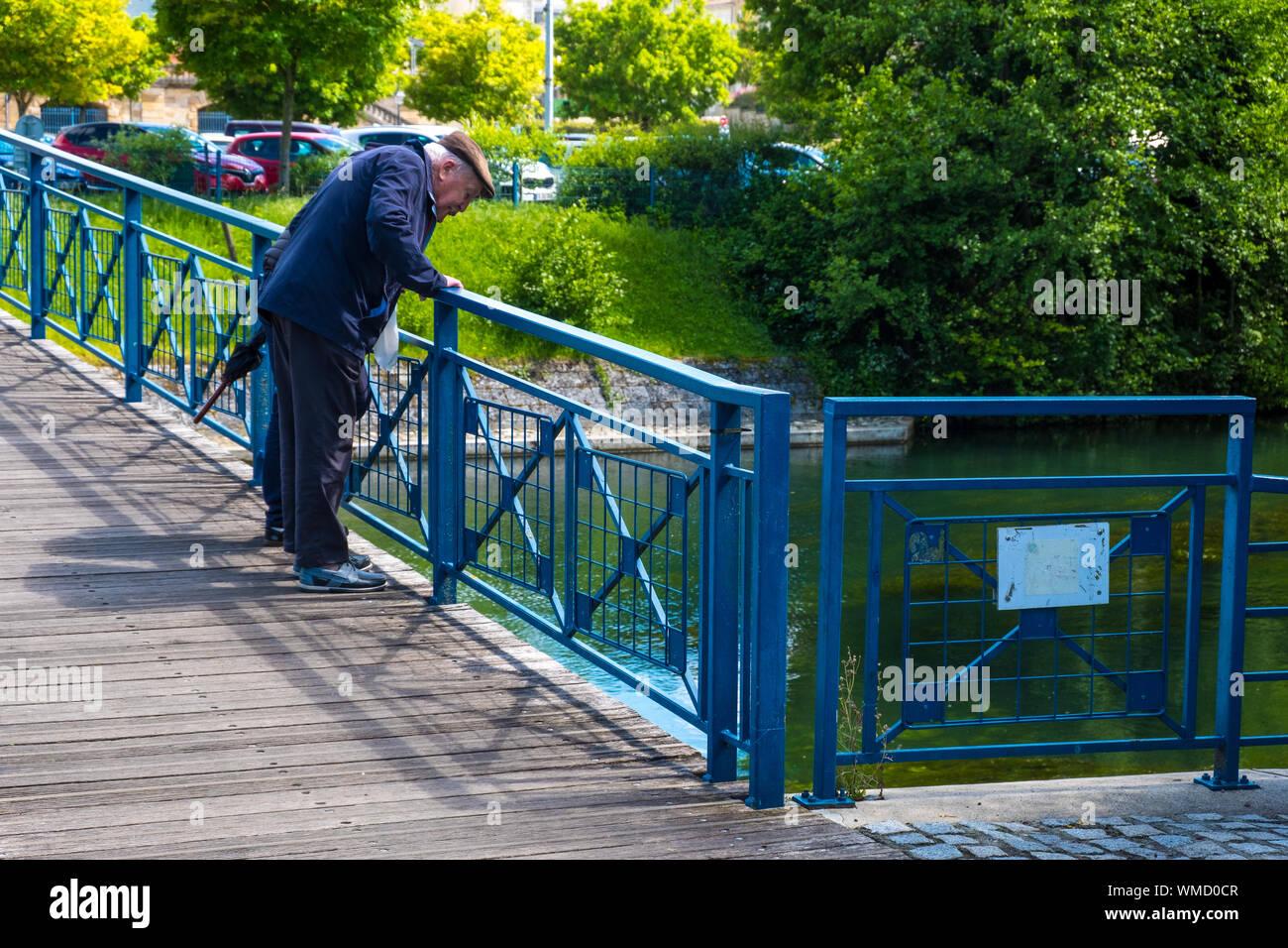 Niort, Francia - 11 de mayo de 2019: el anciano en un puente sobre un río de Sevres, en la parte vieja de la ciudad de Niort, Deux-Sevres, Francia Foto de stock