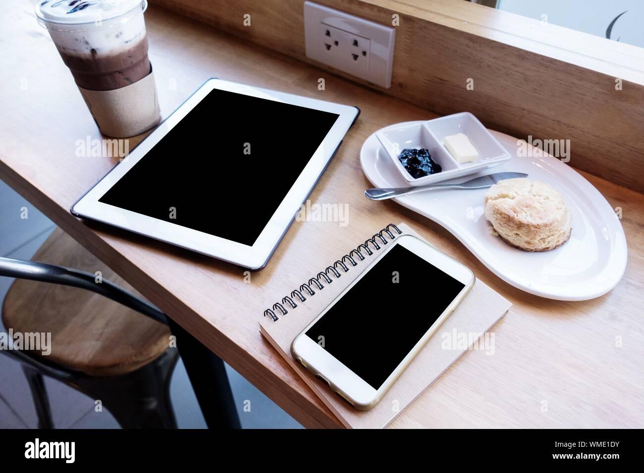 Teléfono inteligente con un café en la mesa del café Foto de stock