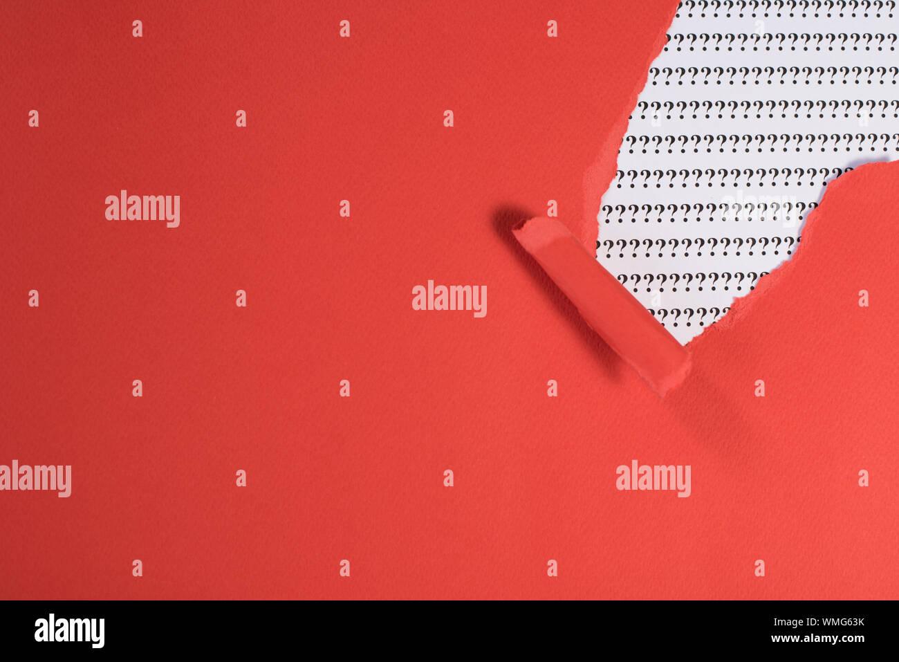 Papel rojo teared revelando interrogación sobre papel blanco. Concepto de FAQ, Q&A, buscar riddle e información Foto de stock