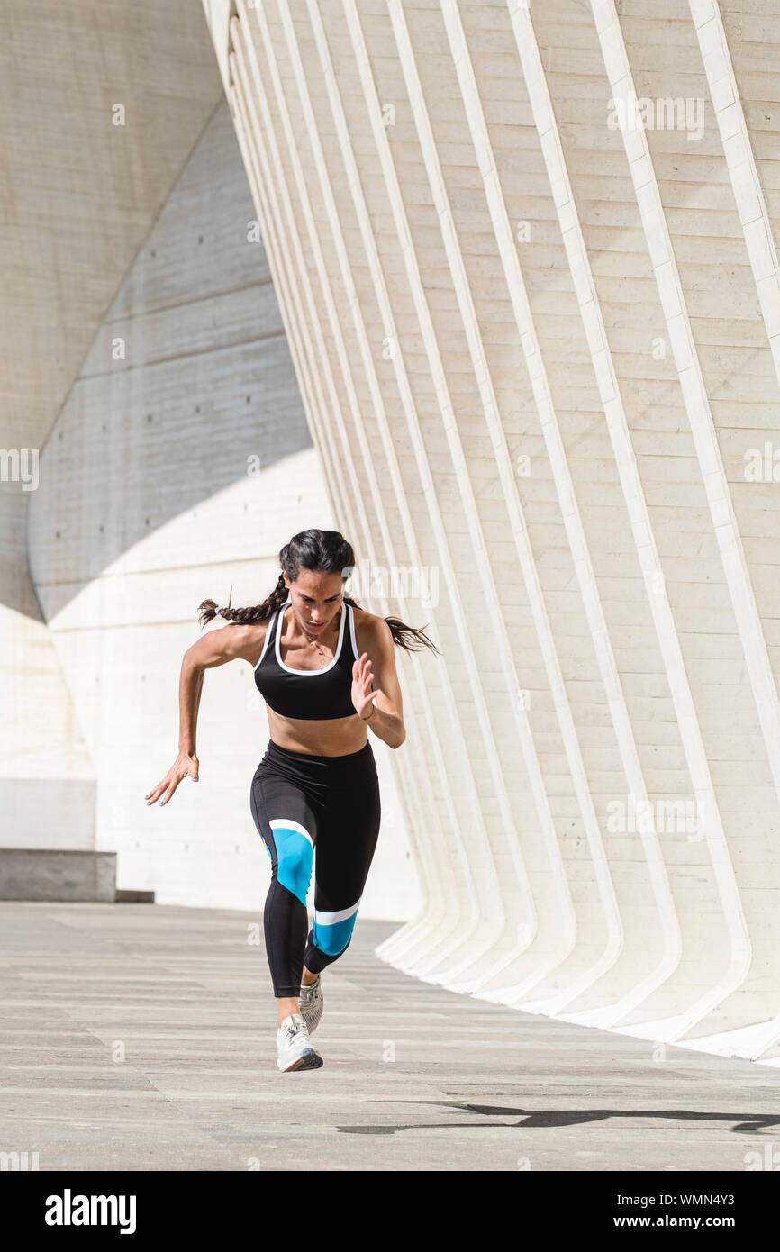 De cuerpo completo atleta femenina en ropa deportiva corriendo sobre hormigón Foto de stock