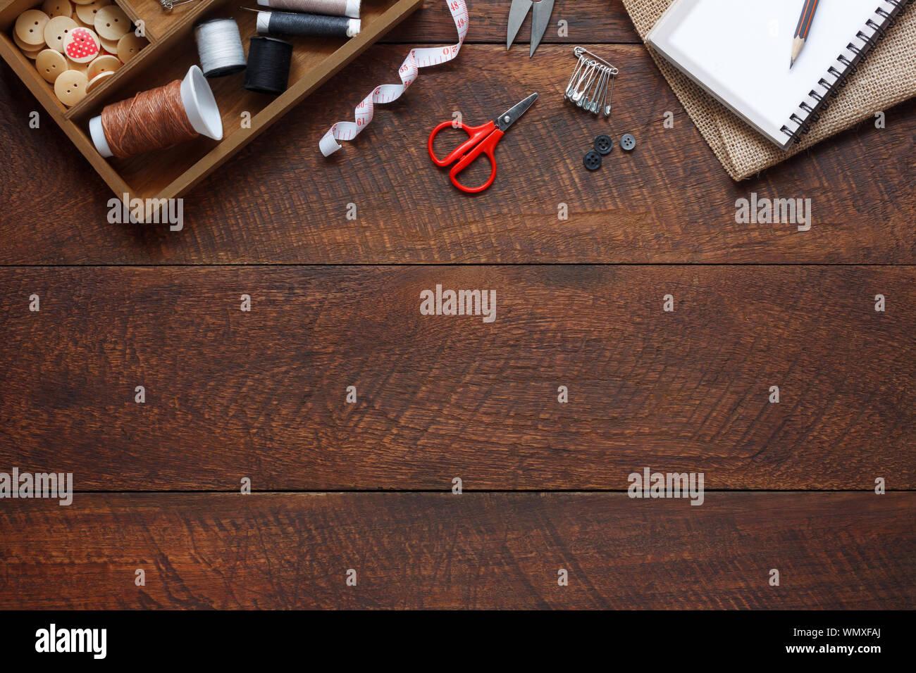 Imagen aérea laicos plana del diseñador de moda artículos concepto de fondo.La vista superior o adaptar accesorios de costura en equipos modernos rústicos de madera marrón en casa Foto de stock