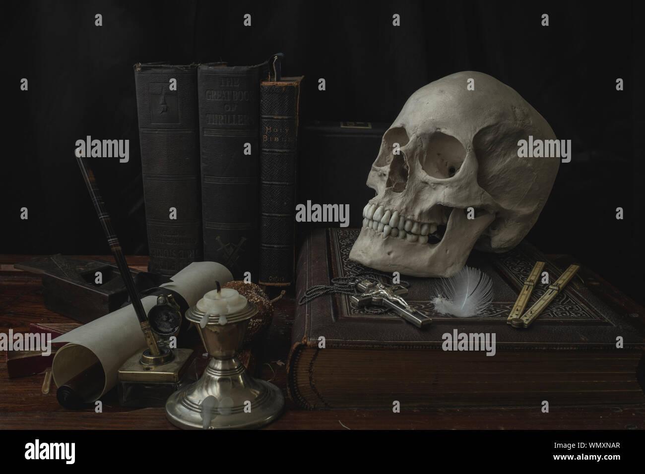 Close-up de cráneo humano con la cruz sobre el libro en la mesa Foto de stock
