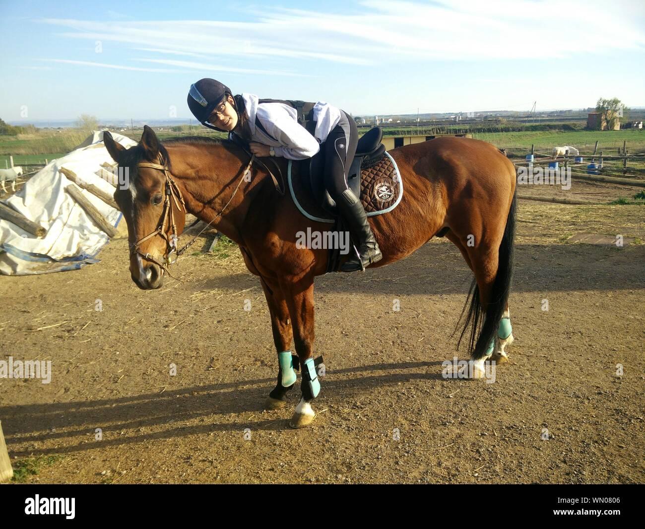 Vista lateral retrato de adolescente a caballo en el campo Foto de stock